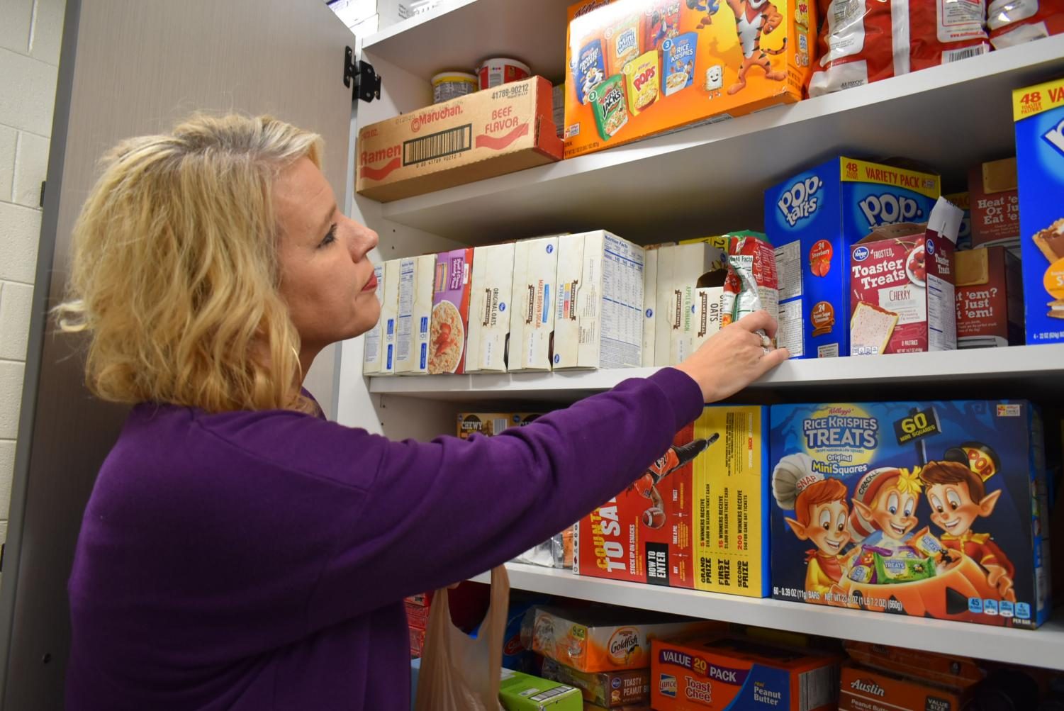 Cheri Risher inventories her food pantry.  The center helps to ensure that no student goes hungry on weekends through a backpack program.