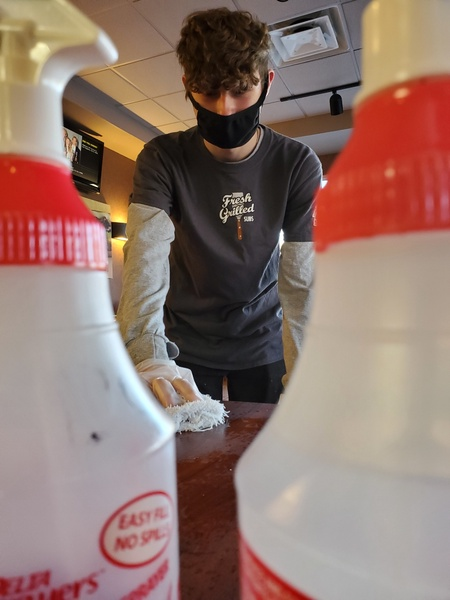 Austin Monroe sanitizes tables in between guests at his part-time job.  The extra safety protocols have increased the work load and stress for many high school workers.